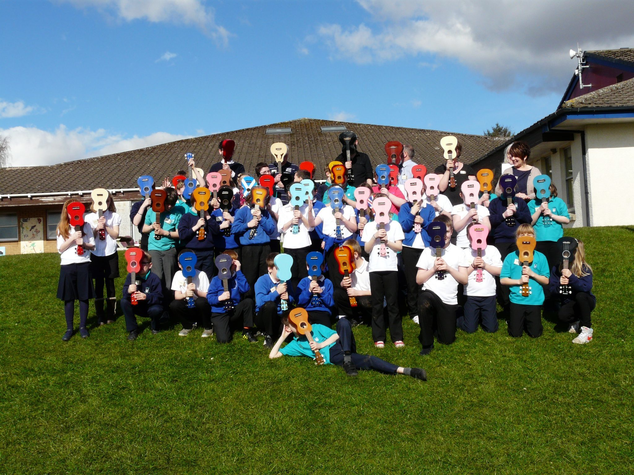 Pupils hold ukuleles in front of their faces for a funny group photo.