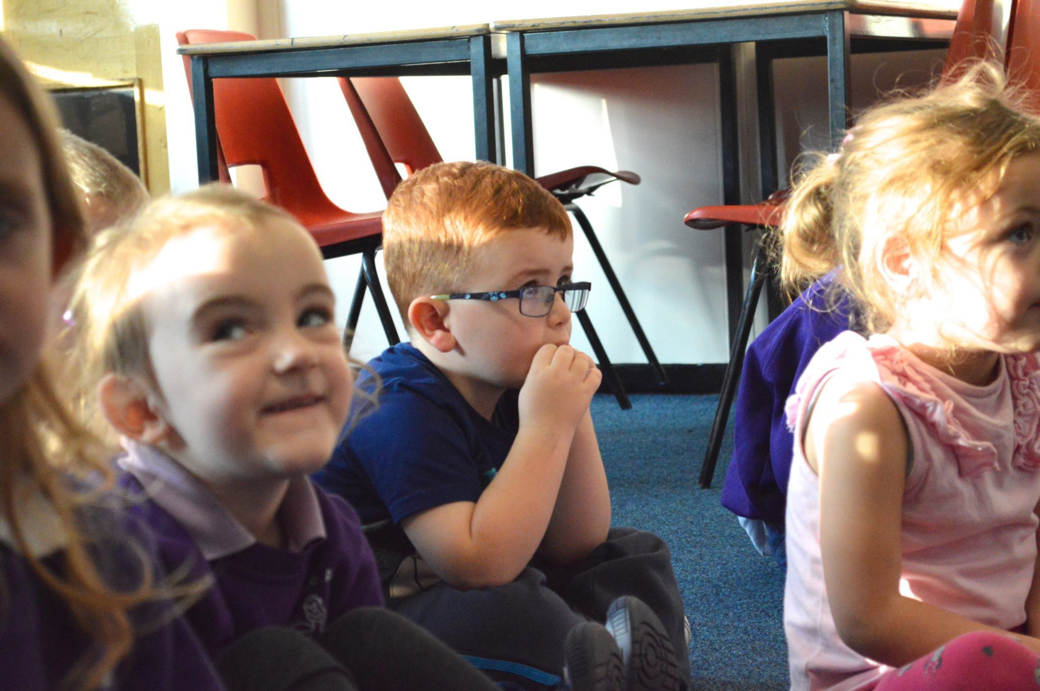 A young pupil listens attentively to a story.