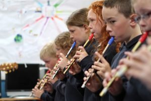 Young tin whistle players stand in line and play a tune together.