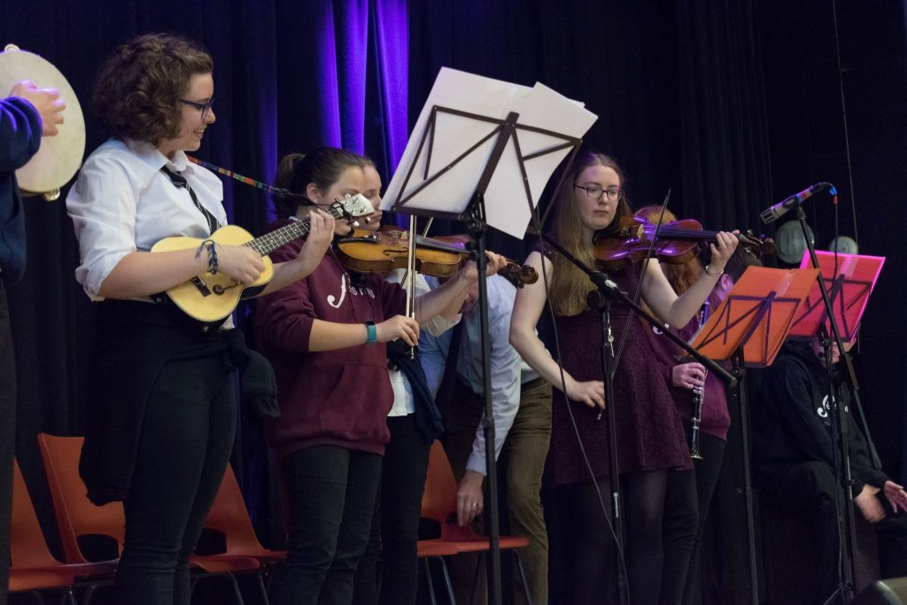 Musicians from Banff Academy's Trad Band perform on stage.